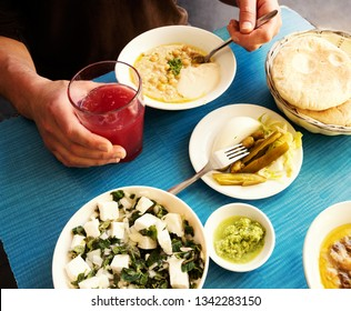Man eating fresh warm hummus with pita bread, pickles, feta cheese salad with organic herbs and drinking fresh squeezed fruit juice. Healthy eating middle eastern cuisine background.  Foodie travel.