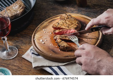 Man is eating grilled steak at a wooden table. Dinner table concept