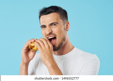 A man eating a hamburger on a blue background wide open mouth short cut white t-shirt