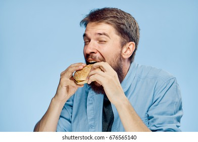Man eating a hamburger on a blue background