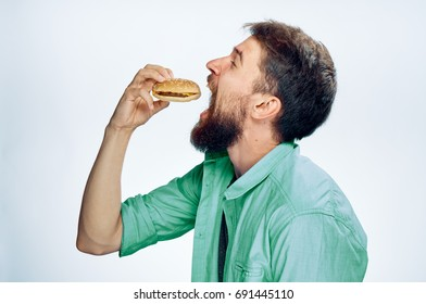Man eating a hamburger on a light background profile