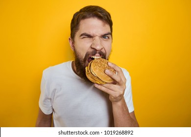 man eating a hamburger on a yellow background