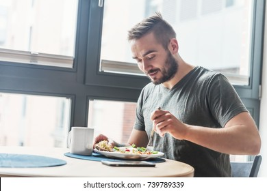 A man eating a healthy morning meal, breakfast at home. Fit lifestyle. - Shutterstock ID 739789339