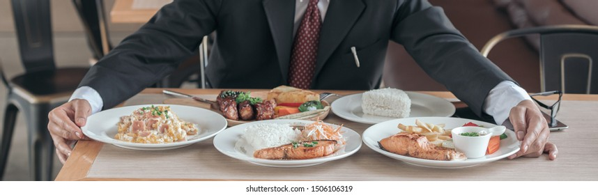 Man eating lots of food on the table with fired fish, pork steak, steam cooking rice, health care concept.