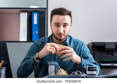 A man eating lunch while working and looking at the laptop screen