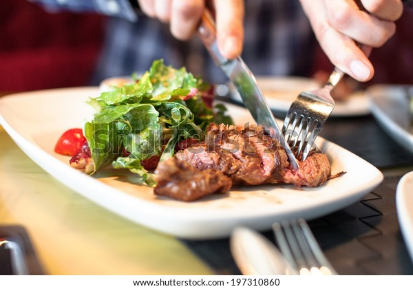 man eating meat with salad