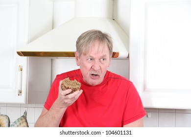 man is eating a peace of bread in the kitchen