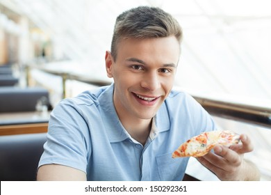 Man eating pizza. Cheerful young man eating pizza at the restaurant