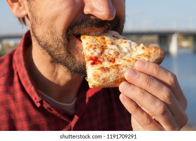A man is eating pizza in nature