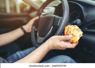 Man eating a pizza while driving car.