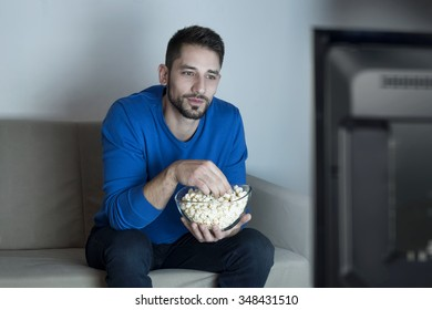 Man eating pop corn watching television