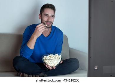 Man eating pop corn watching movies