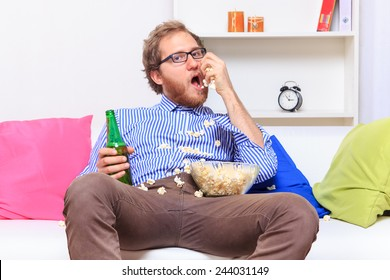Man eating popcorn on the sofa - studio shoot