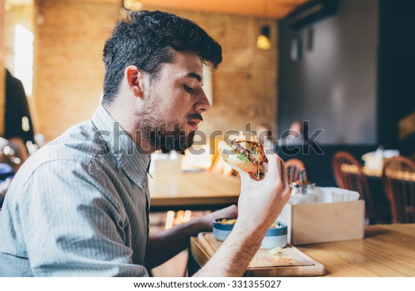 Man is eating in a restaurant and enjoying delicious food