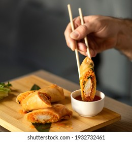Man Eating Rolls with Sauce Using Chinese Chopsticks. Delicious oriental dish, close up. Eastern Cuisine. Food concept. Square format or 1x1 for posting on social media. Soft focus.