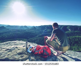 Man eating sandwich and apple while rest on rocky mountain peak and enjoy marvelous view into wild nature.
