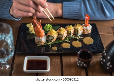 Man is eating sushi in the black plate on a wooden table. Rolls close-up.