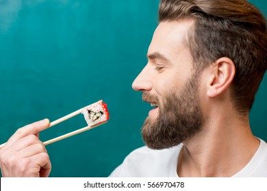 Man eating sushi with chopsticks on the green background