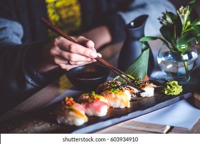 Man eating sushi set with chopsticks on restaurant