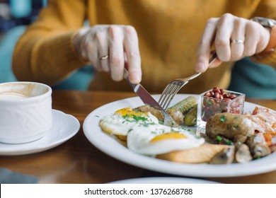Man eating traditional English breakfast with fried eggs, sausages, beans, mushrooms, bacon at cafe in the morning.
