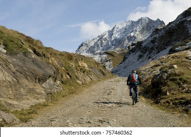 man with an ebike, electric bike, mountains covered with fresh snow just fall, autumn, observes Kastelhorn (Castel Peak), grass, dirt, October, Alps, light, clouds, Formazza valley, Piedmont, Italy