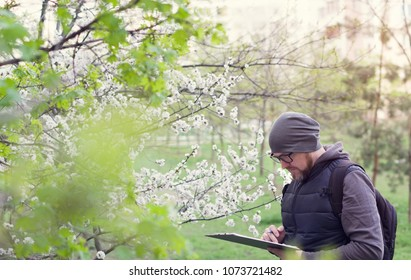 Man ecologist conducts research during the flowering of trees. Agronomist - breeder  in the garden.