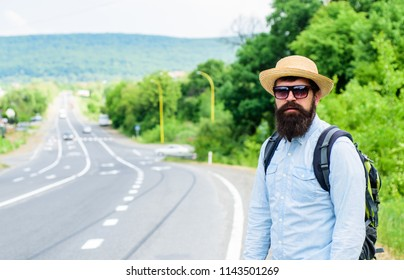 Man at edge of highway looking for transport. On the road. Hitchhiking means transportation that gained asking strangers for ride in their car. Hitchhiker try to stop transport to get to destination.