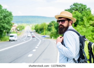 Man at edge of highway wait transport. Travel alone. Hitchhiking means transportation gained asking strangers for ride in their car. Hitchhiker travel alone try stop transport to get to destination.