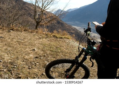 man with an electric bicycle, e-bike, ebike, check the map path on mobile phone, mountains, autumn, sunset, Piedmont, Ossola Valley, Italy