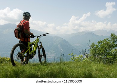 man with electric bicycle, e-bike, ebike, high mountains, observes valley,