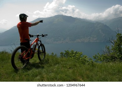 man with electric bicycle, e-bike, ebike, indicate mountains, valley, lake of Como, summer, sport, cloud, sun, alps, Lombardy, Italy