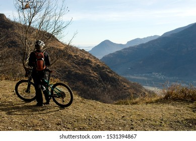 man with an electric bicycle, e-bike, ebike, looking mountains, autumn, sunset, Piedmont, Ossola Valley, Italy