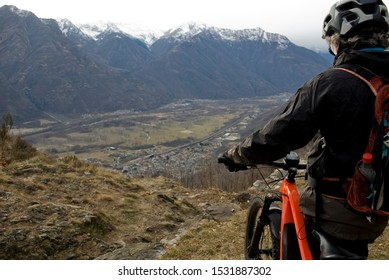man with an electric bicycle, e-bike, ebike, looking mountains covered by first snow, autumn, sunset, Piedmont, Ossola Valley, Italy