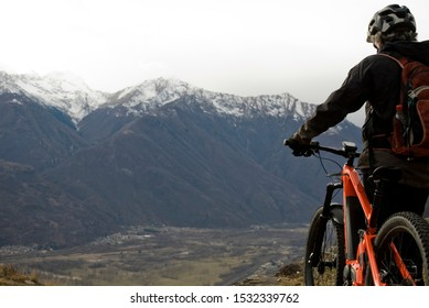 man with an electric bicycle, e-bike, ebike, looking mountains covered by the first snow, autumn, sunset, Piedmont, Ossola Valley, Italy