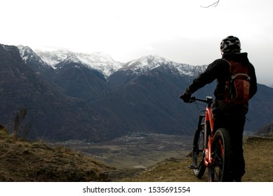 man with an electric bicycle, e-bike, ebike, looking mountains covered by snow, autumn, Piedmont, Ossola Valley, Italy