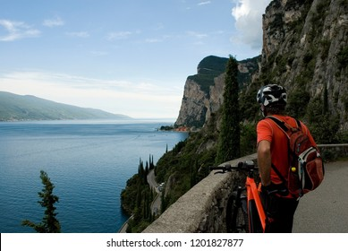 man with an electric bicycle, e-bike, ebike, mtb, look sunset on Lake Garda, mountain, summer, sport, adventure, freedom, alps, travel, Lombardy, Italy