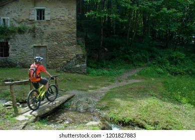 man with an electric bicycle, e-bike, ebike, mtb, on a small wooden bridge to cross a river, summer, mountain, sport, adventure, freedom, alps, Como Lake forest, Italy
