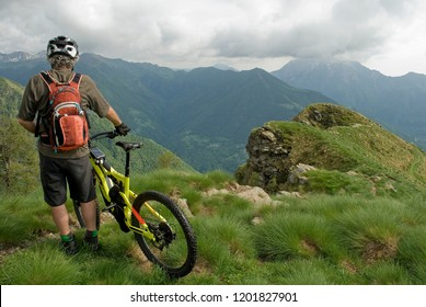 man with an electric bicycle, e-bike, ebike, mtb, look valley and mountains forest, summer, sport, adventure, alps, Mount Legnone, Como Lake, Italy