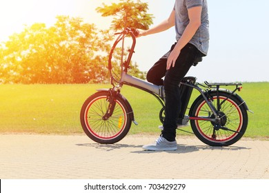 A man with electric bicycle in a park