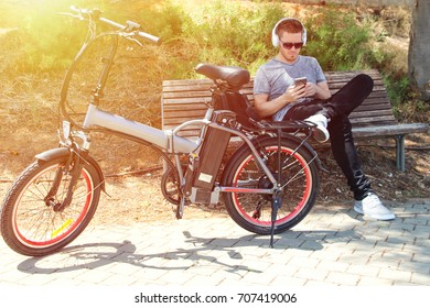 Man with electric bicycle sitting in the park with headphone