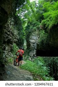 man with an electric bike, e-bike, ebike, mtb, mountain, rock canyon created by a river, summer, sport, adventure, alps, Path, Garda Lake, Italy