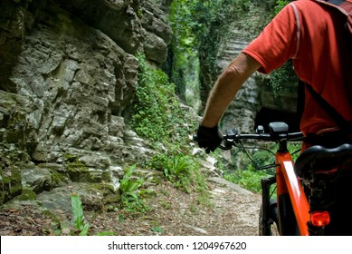 """man with an electric bike, e-bike, ebike, mtb, mountain, rock canyon created by a river, summer, sport, adventure, freedom, alps, Path called """"Strada della Forra"""", Garda Lake, Lombardy, Italy"""