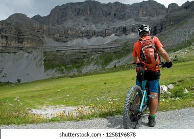 man with an electric bike, e-bike, ebike, mtb, rock, mountain, Dolomites, Madonna di Campiglio, summer, sport, adventure, alps, travel, Trentino Alto Adige, Italy