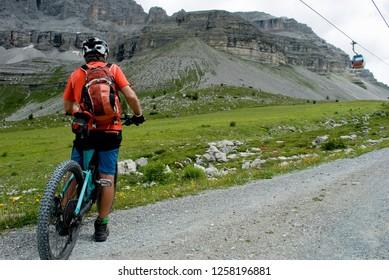 man with an electric bike, e-bike, ebike, mtb, rock, mountains, Dolomites, unesco heritage, Madonna di Campiglio, summer, sport, adventure, alps, travel, Trentino Alto Adige, Italy