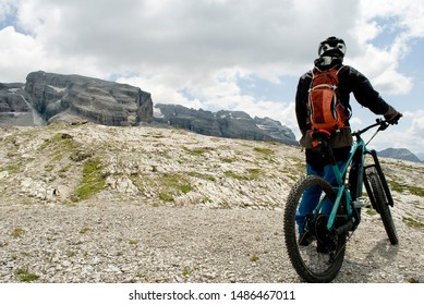 man with an electric bike, e-bike, ebike, mtb, observes Grosté Peak, Dolomite mountains, Madonna di Campiglio, summer, sport, adventure, travel, Alps, Trentino, Alto Adige, Italy