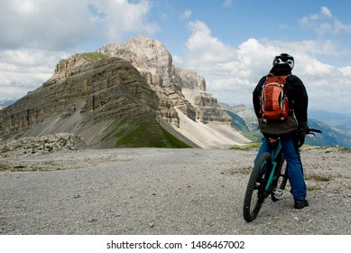 man with an electric bike, e-bike, ebike, observe Pietra Grande Peak and Grosté Pass, Dolomite mountains, Madonna di Campiglio, summer, sport, adventure, travel, Alps, Trentino, Italy