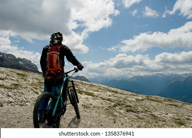 man with an electric bike, e-bike, ebike, observes Dolomites mountains, Madonna di Campiglio, summer, sport, adventure, travel, Alps, Trentino, Italy