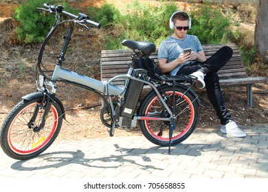 Man with electric e bike sitting in the park with headphones and phone