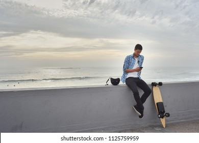 Man with electric skateboard at the beach
