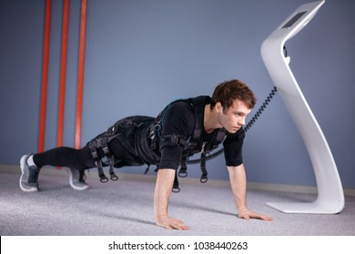 man in Electrical Muscular Stimulation suits doing plank exercise. EMS. Workout.